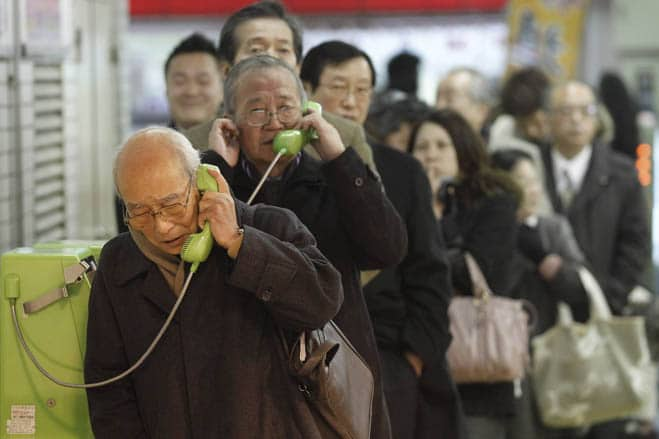Stranded people stand in a line to use public telephones at a train station after subway and train services were suspended after an earthquake, in Tokyo March 11, 2011. The biggest earthquake to hit Japan on record struck the northeast coast on Friday, triggering a 10-metre tsunami that swept away everything in its path, including houses, ships, cars and farm buildings on fire.    REUTERS/Kim Kyung-Hoon (JAPAN - Tags: DISASTER ENVIRONMENT IMAGES OF THE DAY BUSINESS TRANSPORT)